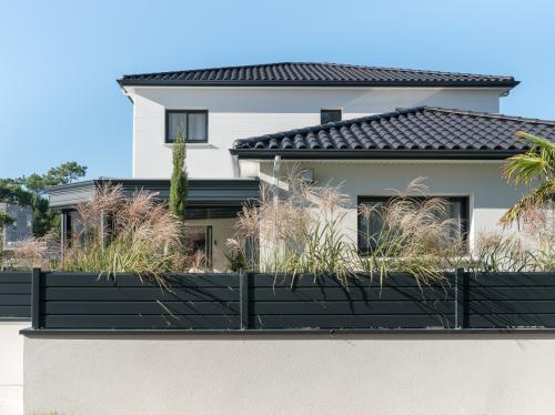 Grande maison à tuiles noires avec véranda